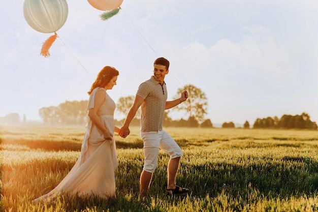 ヘリウム色のボールでフィールドを歩いて愛するカップル