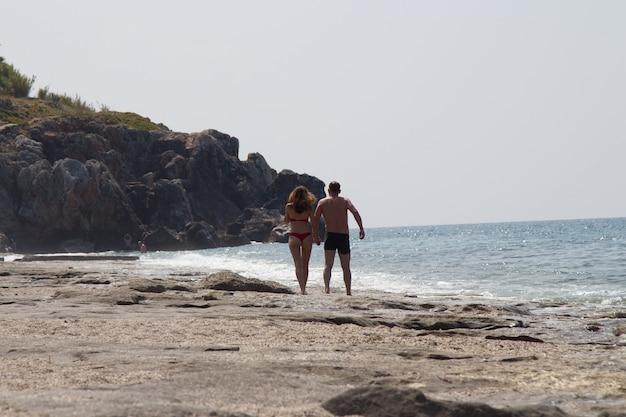 砂浜の砂浜のビーチフロントを歩く愛情のあるカップル。赤い水着を着た赤い髪と黒い水泳パンツを着た男性のほっそりした美しい女性。南国の海の休日