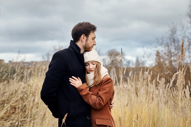 Loving couple walking in park in autumn hugs and kisses. autumn walk men and women in the woods on the fallen leaves. romance and love on an autumn landscape