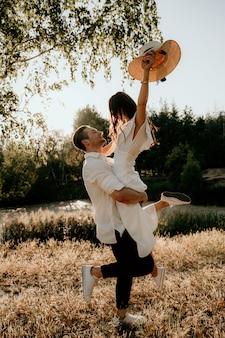 Влюбленная пара ходит и работает на закате летом на природе. брюнетка девушка в шляпе и легкое платье. история о любви.