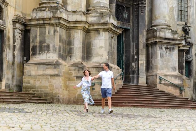 愛するカップルが古い教会に対して手で歩きます。