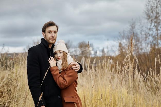 愛するカップルが秋の公園を散歩し、抱擁とキスをします。春の森の中で男の腕の中で女性。恋人たちはお互いを愛し、抱きしめます