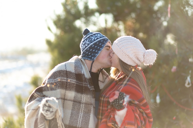 A loving couple in warm plaids kisses holding sparklers in their hands