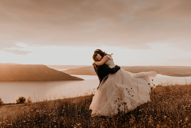 Loving couple wedding newlyweds in white dress and suit hug kissing whirl on tall grass in summer field on mountain above the river