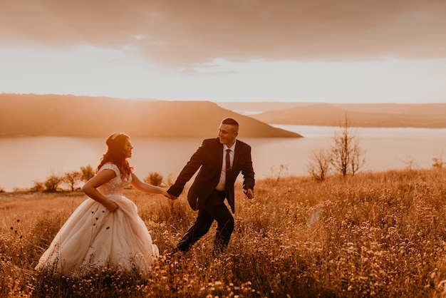 A loving couple wedding newlyweds in a white dress and a suit walk run smile happy on tall grass in the summer field on the mountain above the river