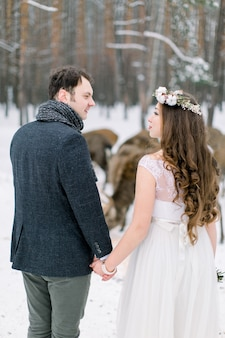 Loving couple on weeding day with herd of deer