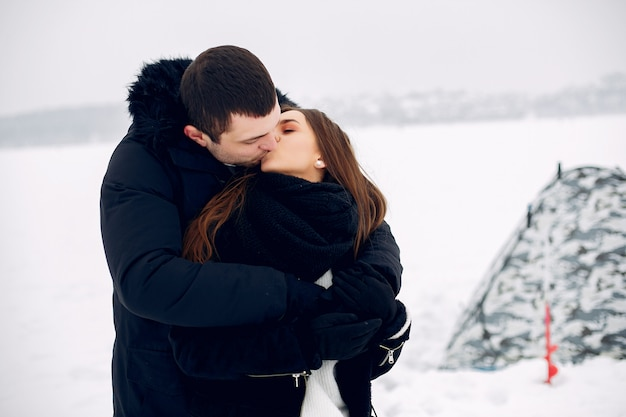 Loving couple in a winter clother standing on ice