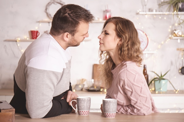 Loving couple in winter clothes in the kitchen