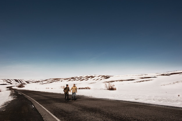Loving couple in the winter runs on the road among the mountains. man and woman running down the road. winter journey. a couple in love travels.