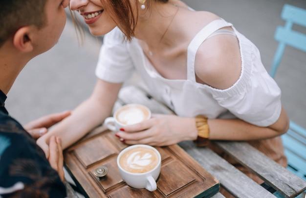 Влюбленная пара с кофе на улице за столом, взявшись за руки, улыбаются друг другу