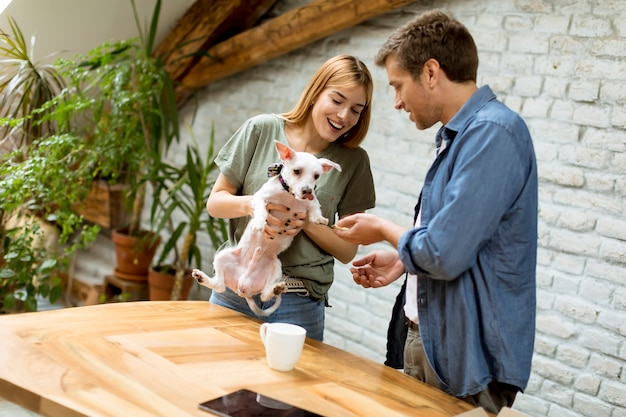 Loving couple with cute white dog in the room