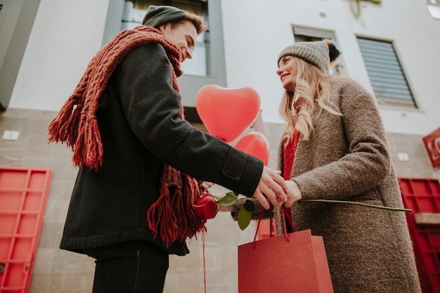 Loving couple with gifts and balloons on street