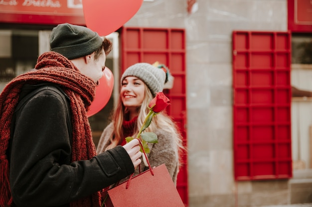 Loving couple with gifts on street