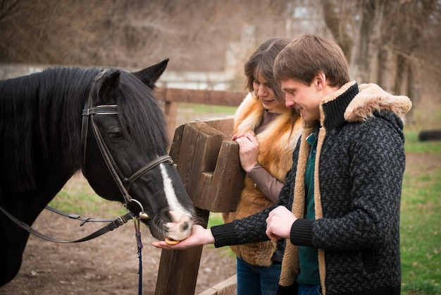 Loving couple with a horse on ranch in an autumn cloudy day.