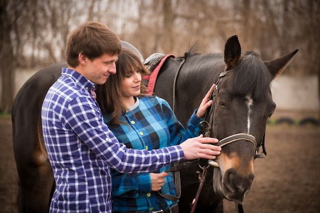 Loving couple with a horse on a ranch in an autumn cloudy day.