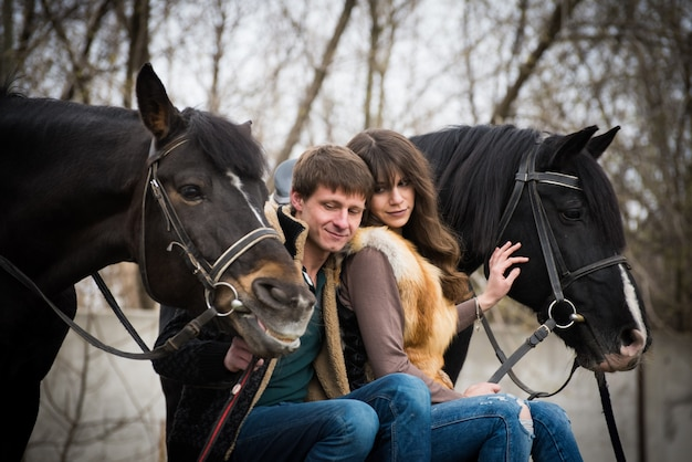 Loving couple with horses on a ranch in an autumn cloudy day.