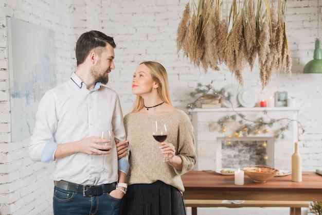 Влюбленная пара с бокалами в помещении