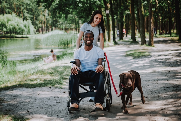Loving couple woman pushing wheelchair for man