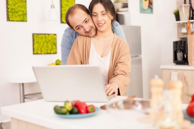 식탁에 신선한 야채와 함께 부엌에서 노트북 작업을 하는 사랑스러운 부부. 현대적인 wi-fi 무선 인터넷 기술을 사용하여 집에서 사랑하는 부부의 행복한 사랑의 쾌활한 낭만적인