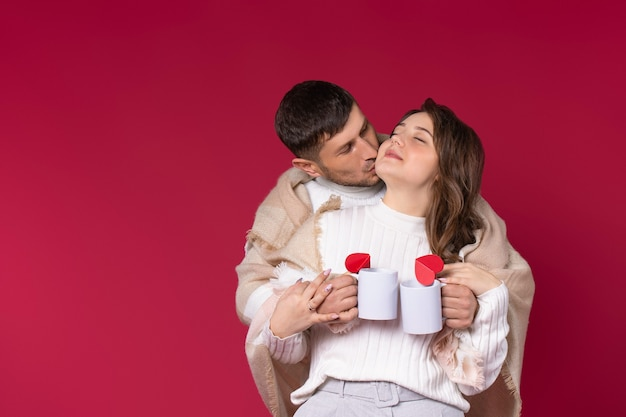 A loving couple wrapped in a warm blanket holds hot tea cups. red background.