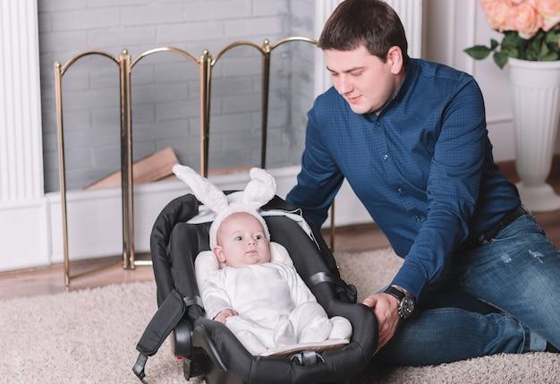 산책하기 전에 토끼 의상을 입은 사랑하는 아빠와 예쁜 아기