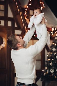 Любящий папа в белом джемпере играет с новорожденным, держа его или ее в воздухе на руках