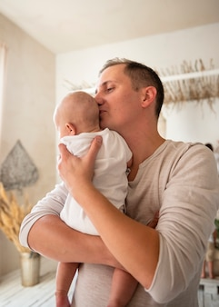 Loving dad with newborn indoors