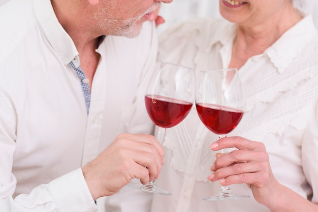 Loving elder couple enjoying red wine at home
