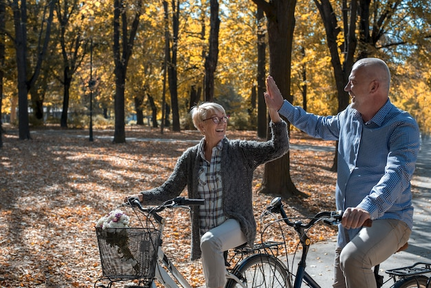 Loving elderly couple high-fiving each other while riding a bicycle in the park
