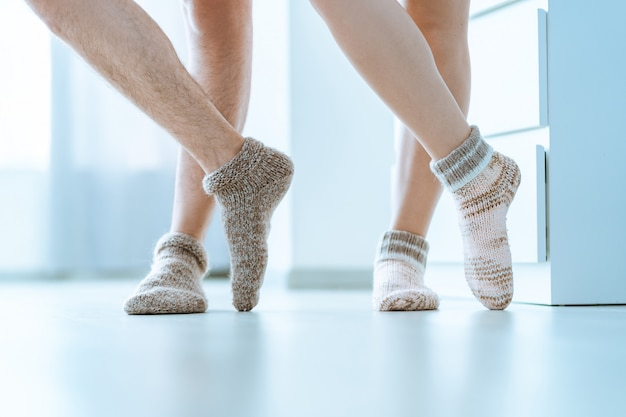 Loving family couple together in cozy soft comfortable knitted winter socks at home
