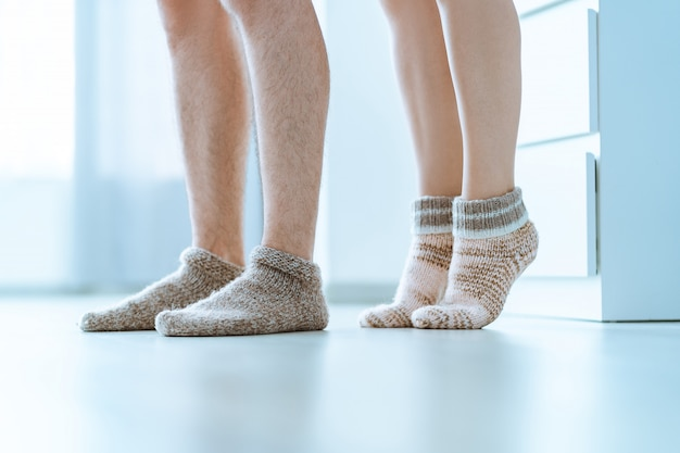 Loving family couple together in cozy soft warm knitted winter socks at home