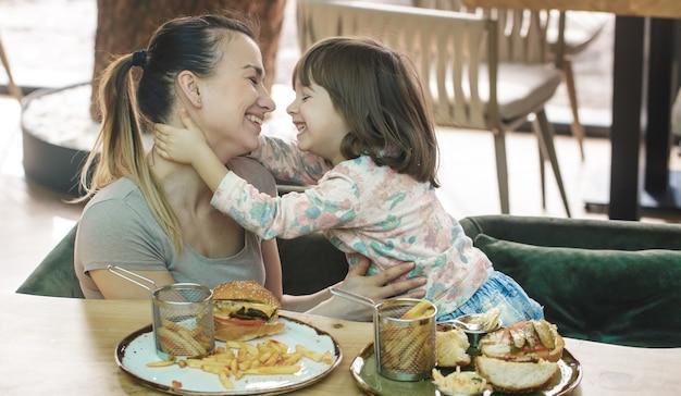 愛する家族。カフェ、家族、栄養の概念でファーストフードを食べるかわいい娘を持つお母さん