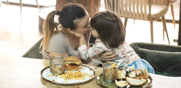 Любящая семья. мама с милой дочерью ест фаст-фуд в кафе, концепция семьи и питания