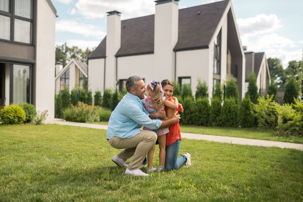 사랑하는 가족. 주말에 즐거운 시간을 보내면서 귀여운 소녀를 안고 있는 부모