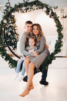 Любящая семья, прижимаясь к рождеству качели. рождественская елка.