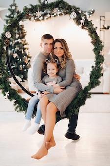 Любящая семья, прижимаясь к рождеству качели.