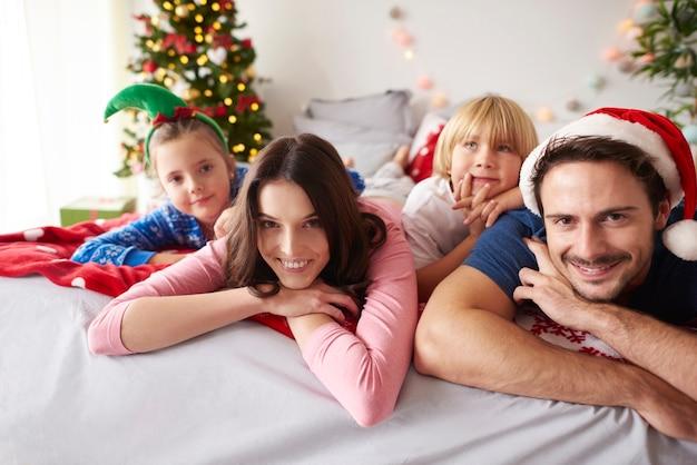 Loving family spending christmas in bed