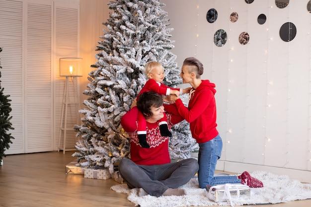 部屋にプレゼントを持っている愛する家族。メリークリスマスとハッピーホリデー。屋内で楽しんでいる親とその小さな子供。