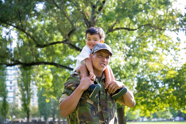 Loving father holding son on neck and walking in city park. happy caucasian son sitting on neck of dad in uniform, hugging him and looking away. family reunion, fatherhood and returning home concept