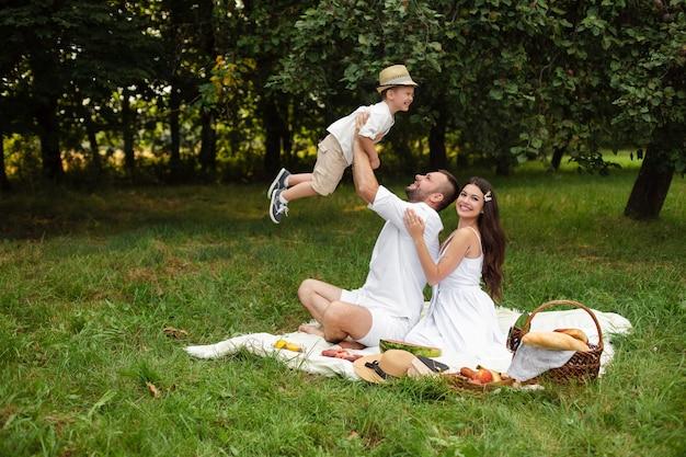 아름다운 어머니가 남편을 뒤에서 껴안는 동안 아들과 함께 노는 사랑하는 아버지. 잔디에 피크닉에 공원이나 숲에서 여름날을 즐기는 행복 한 백인 가족.