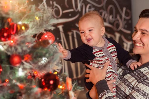 一緒に笑っているクリスマスツリーの近くで息子と愛情のある父
