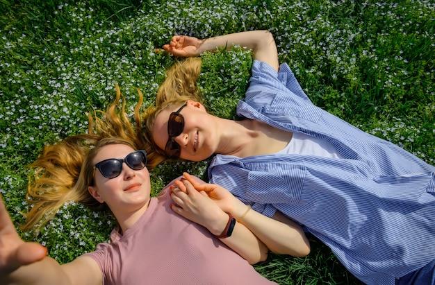 Любящая женская пара, лежа лицом к лицу на лугу и держась за руки