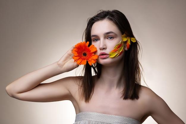 愛する花。花を愛するオープンショルダードレスを着ている若い魅力的な黒髪の女性