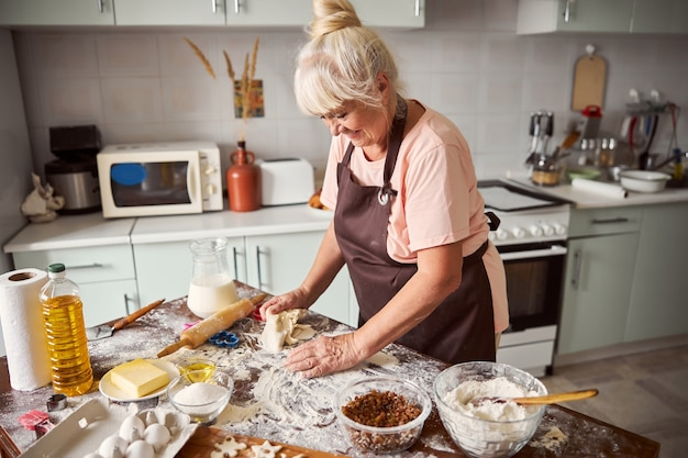 그녀의 부엌에서 쿠키 반죽을 만드는 사랑 할머니