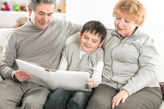 Loving grandparents with grandchild sitting on sofa