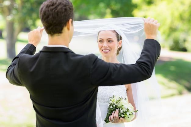 Loving groom lifting veil of bride