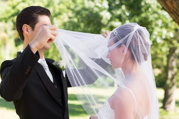 Loving groom unveiling bride in garden