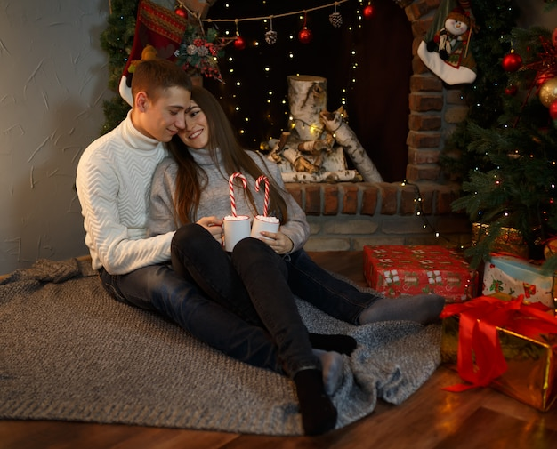 Loving guy and his girlfriend are sitting on the floor in the house near the fireplace on christmas eve