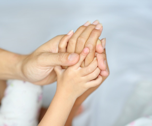 Loving hands clasped of family father, mother and daughter.