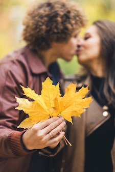 Loving happy couple in autumn in park holding autumn maple leaves in hands